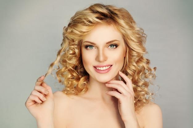 Ładna dziewczyna z kręconymi włosami i uśmiechem toothy. białe zęby, blond włosy