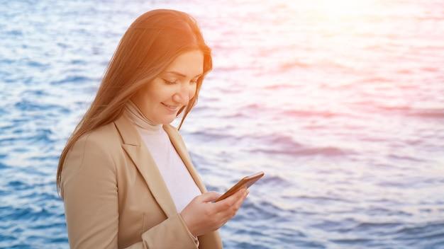 Ładna dziewczyna z machaniem w długich włosach stoi na plaży, rozmawiając z przyjaciółmi na gadżecie na tle błękitnego morza