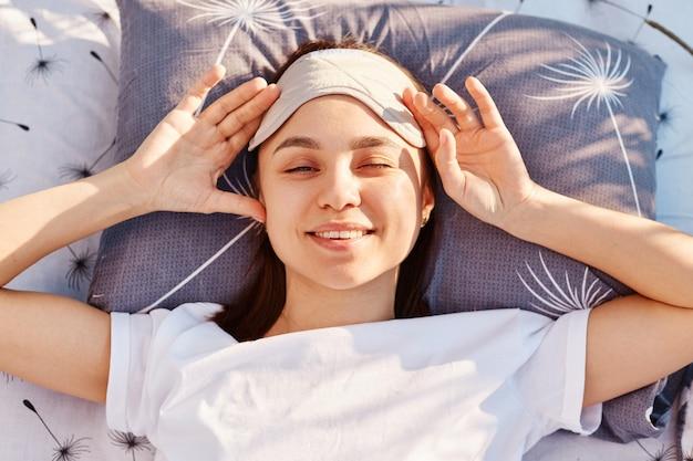 Ładna dziewczyna z maską do spania na czole, ubrana w białą koszulkę w stylu casual, leżącą na miękkim łóżku na środku łąki, patrząc na kamerę z uśmiechem, światło słoneczne świeci w oczy.