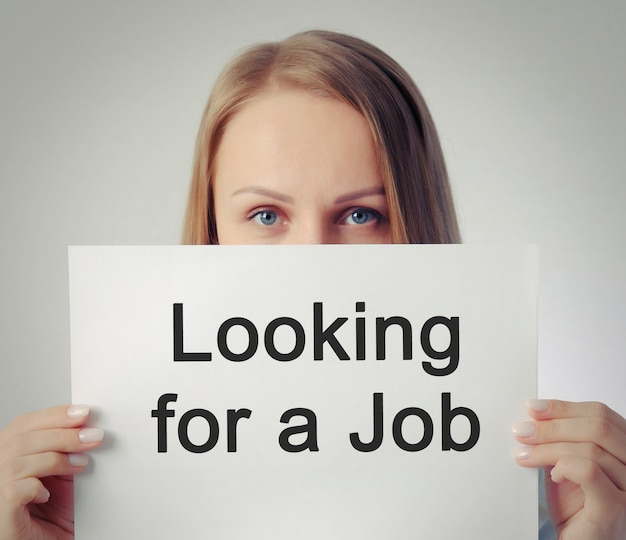 Ładna dziewczyna z napisem szuka pracy
