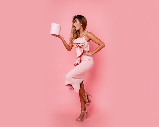 Ładna dziewczyna z niespodzianką, trzymając pudełko i stojącą nad różaną ścianą w eleganckiej różowej sukience. ekstatyczne emocje.