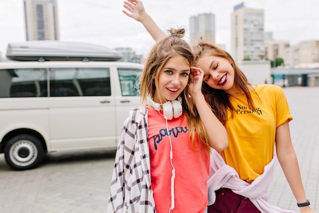 Ładna dziewczyna z pięknym wyrazem twarzy dotykając włosów, podczas gdy jej roześmiana przyjaciółka w żółtej koszuli tańczy w tyle
