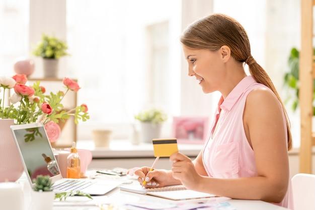 Ładna dziewczyna z plastikową kartą patrząc na wyświetlacz laptopa i robiąc notatki, idąc coś kupić w sklepie internetowym
