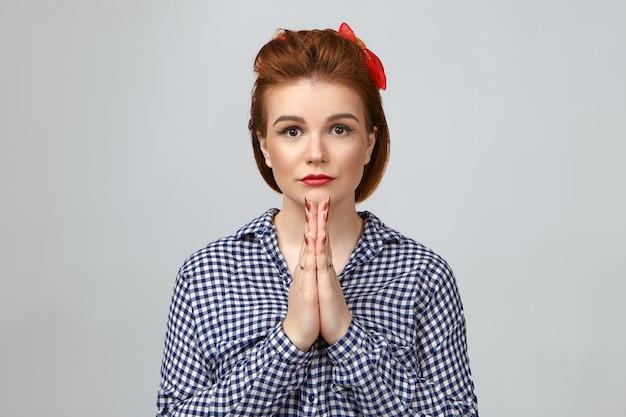 Ładna dziewczyna z rudymi włosami i czerwoną szminką, ściskając dłonie razem w modlitwie. dobrze wyglądająca stylowa młoda kobieta modli się w studio, wpatrując się w kamerę z wielkimi oczami pełnymi nadziei i silnej wiary