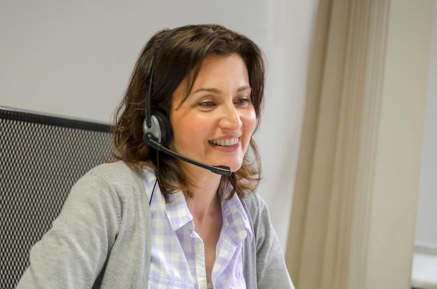 Ładna dziewczyna z słuchawkami rozmawiać i uśmiechać się. połącz się z komputerem internetowym