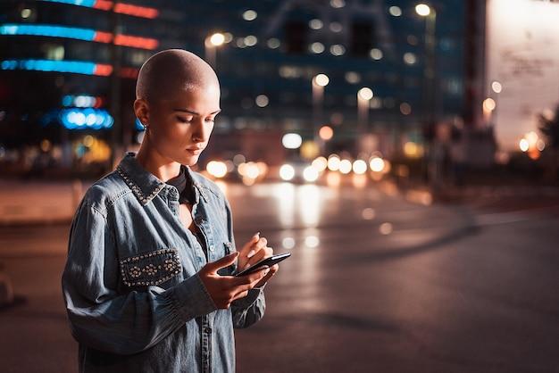 Ładna dziewczyna z stylowe ubrania trzymając smartfon na zewnątrz wieczorem, oświetlone miasto