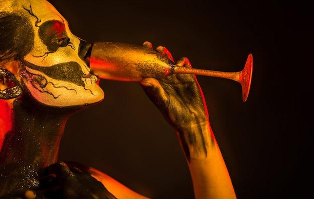 Ładna dziewczyna z szkielet makijaż trzyma szkło