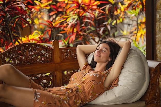Ładna dziewczyna z uśmiechem na twarzy, ciesząc się ciszą natury na wyspie