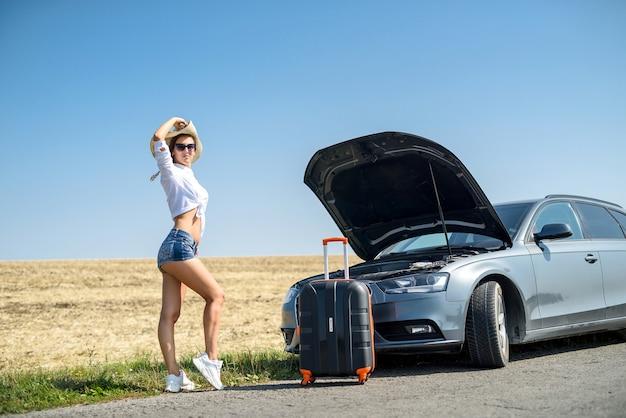 Ładna dziewczyna z walizką stojącą obok samochodu i wiatu na wymarzonej podróży