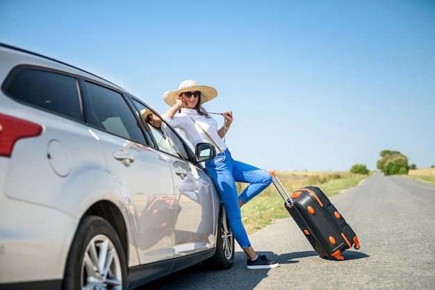 Ładna dziewczyna z walizką stojąca w pobliżu samochodu i wiat na jej wymarzoną wycieczkę.