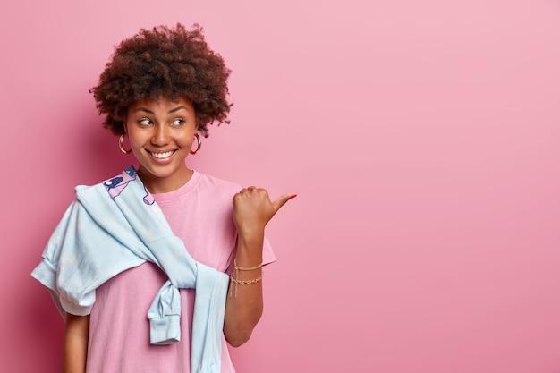 Ładna dziewczyna z włosami afro pomaga wybrać najlepszy wybór, wskazuje kciuk na bok, reklamuje produkt, uśmiecha się radośnie, nosi różową koszulkę i sweter zawiązany na ramieniu. twoja promocja tutaj