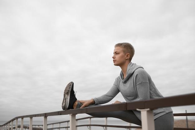 Ładna dziewczyna z wysportowanym ciałem, rozciągająca nogę przy użyciu poręczy na plaży, przygotowująca mięśnie do treningu cardio, posiadająca pewny siebie wygląd. koncepcja ludzie, aktywność, zdrowie, fitness i sport