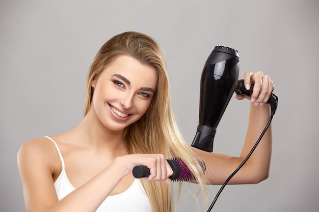 Ładna dziewczyna z zdrowe włosy długie blondy za pomocą suszarki do włosów do prostowania, piękna kobieta trzyma pędzel i suszarkę do włosów