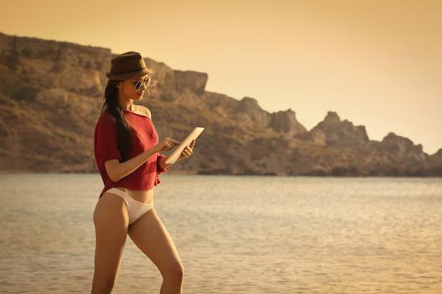 Ładna dziewczyna za pomocą tabletu na plaży