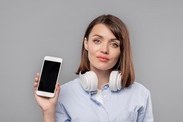 Ładna dziewczyna ze słuchawkami pokazująca reklamę lub promocję na ekranie smartfona w izolacji