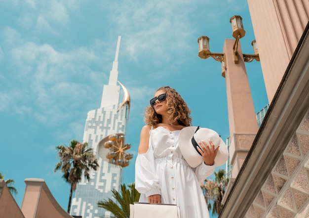 Ładna dziewczyna żeńska zwiedzanie miasta w europie. kręcona kobieta w białej szyfonowej sukience i białym kapeluszu spacerująca wśród słynnych budynków.