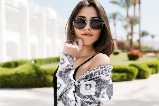 Ładna dziewczyna zmysłowo pozuje dotykając jej twarzy ręką, idąc egzotyczną ulicą. atrakcyjna młoda kobieta z brązowymi prostymi włosami odpoczywa na ośrodek w letni weekend