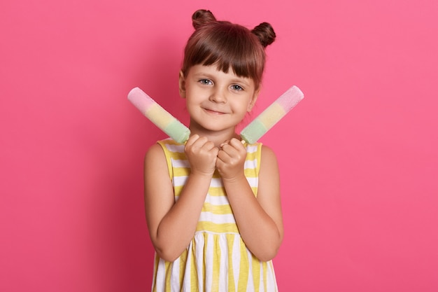 Ładna dziewczynka dziecko trzyma duże lody, dziecko płci żeńskiej wygląda na szczęśliwą, ubrane w żółto-białą sukienkę w paski, mające dwa śmieszne kok do włosów.
