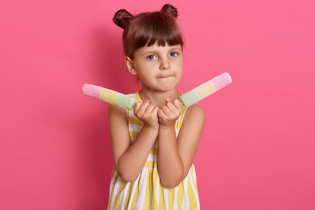 Ładna dziewczynka je, trzymając dwa duże lody, ubrana w biało-żółtą sukienkę, z dwoma koczkami do włosów, pozująca na różowej ścianie z dwoma sorbetami.