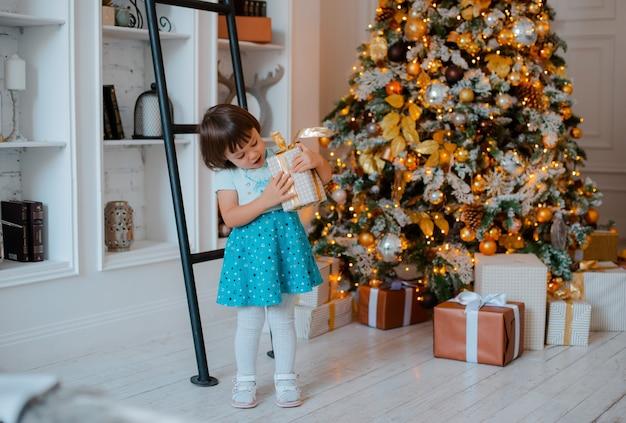 Ładna dziewczynka otwiera świąteczny prezent. portret szczęśliwy dzieciak w wigilię bożego narodzenia.