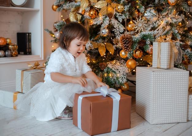 Ładna dziewczynka otwiera świąteczny prezent.