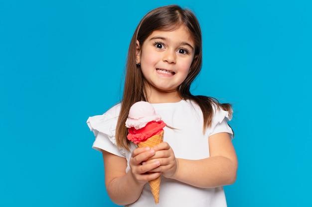Ładna dziewczynka przestraszona wyrazem twarzy i trzymająca lody
