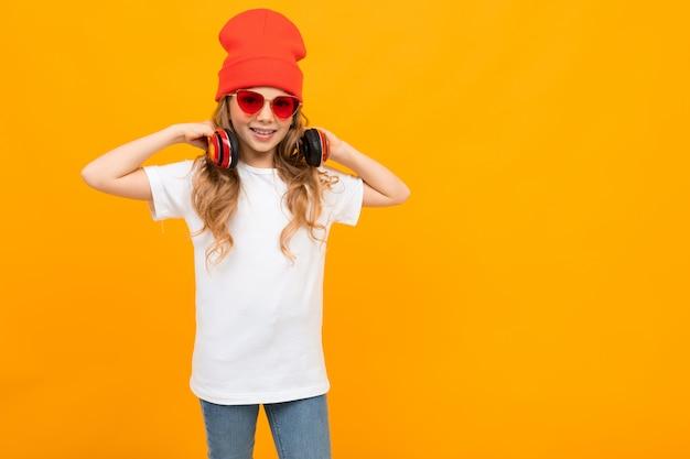 Ładna dziewczynka w białej koszulce, czerwonych okularach przeciwsłonecznych i czerwonym kapeluszu gestykuluje i uśmiecha się na białej ścianie