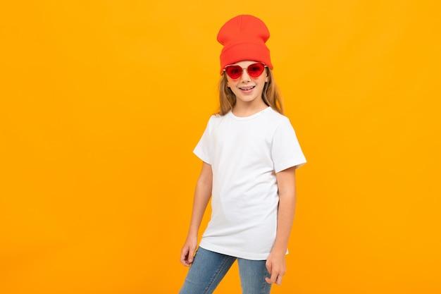 Ładna dziewczynka w białej koszulce, czerwonych okularach przeciwsłonecznych i czerwonym kapeluszu gestykuluje i uśmiecha się na ścianie