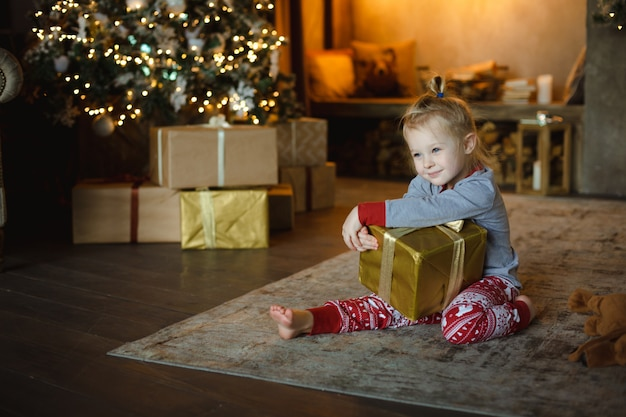 Ładna dziewczynka w tradycyjnej piżamie otrzymała w domu świąteczny prezent na dywanie przed ozdobioną choinką i kominkiem ozdobionym lampkami. rodzinna przytulna koncepcja bożego narodzenia.