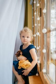 Ładna dziewczynka z jasnymi włosami w niebieskiej sukience trzyma jej śliczną zabawkę i siedzi w pokoju dziecka na parapecie i uśmiecha się