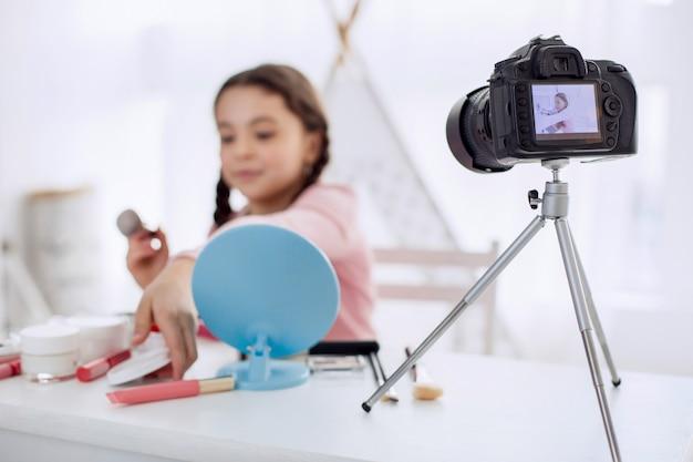 Ładna dziewczynka zachowuje się jak wizażystka przed kamerą
