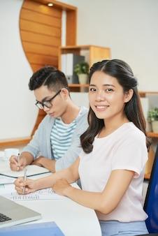 Ładna etniczna kobieta w biurze z kolegą