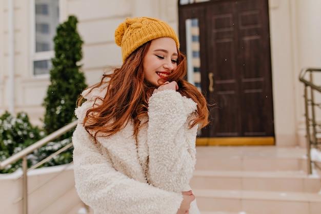 Ładna europejska dama w zimowym płaszczu z czarującym uśmiechem. błoga ruda dziewczyna wyrażająca pozytywne emocje.