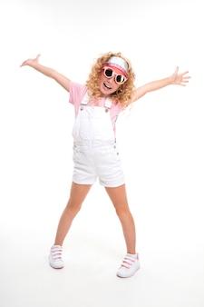 Ładna europejska dziewczyna w okularach przeciwsłonecznych na białej ścianie