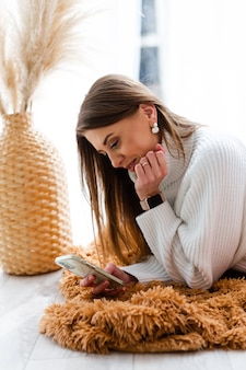 Ładna europejska kobieta w zwykłym białym swetrze leży na podłodze w domu przy oknie z telefonem, pozytywnie rozmawia, prowadzi rozmowę, wysyła wiadomość tekstową