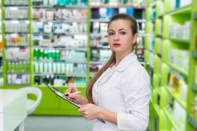 Ładna farmaceuta sprawdzająca listę leków w aptece