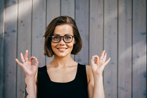 Ładna fitness piękna kobieta z krótkimi włosami w okularach, ubrana na co dzień, pokazując gest ok obiema rękami, wygląda zadowolona na drewnianym tle. koncepcja szczęśliwych ludzi