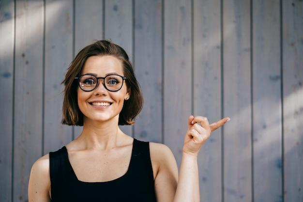 Ładna fitness piękna kobieta z krótkimi włosami w okularach, ubrana na co dzień, wskazując palcem wskazującym na wolną przestrzeń, wygląda zadowolona na drewnianym tle. koncepcja szczęśliwych ludzi