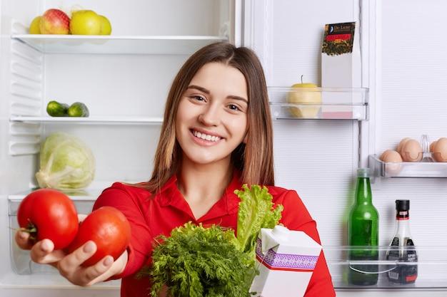 Ładna gospodyni o zachwycającym wyglądzie pokazuje produkty, które kupiła