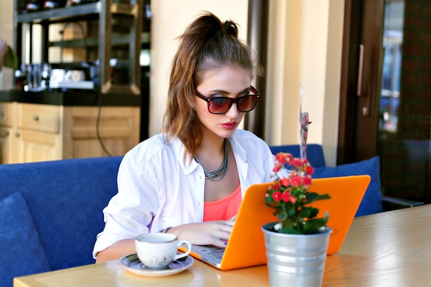 Ładna hipster dziewczyna pracuje na swoim laptopie w miejskiej kawiarni, coworking, młody freelancer dotknij notebooka, letnia atmosfera.