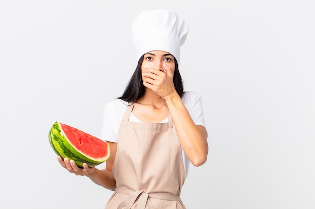 Ładna hiszpańska kobieta kucharz zakrywająca usta rękami zszokowana i trzymająca arbuza