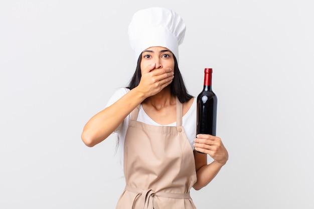 Ładna hiszpańska kobieta szefa kuchni zakrywająca usta rękami zszokowana i trzymająca butelkę wina