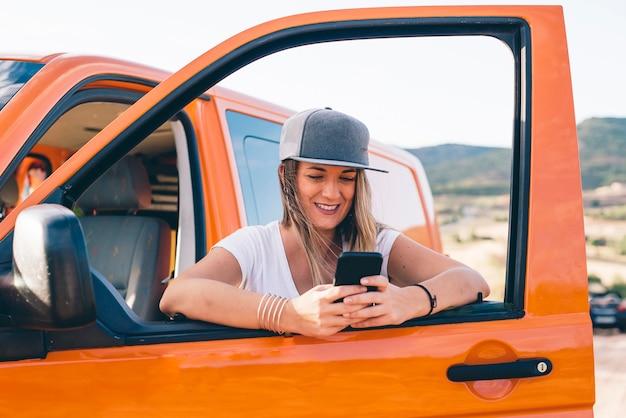 Ładna i atrakcyjna blondynki dziewczyna jest ubranym telefon w pomarańczowej furgonetce z górami z nakrętką