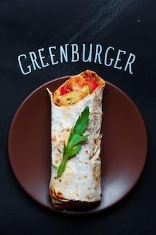 Ładna i gotowa do zjedzenia shaurma lub kanapka z pokrojonymi na pół pomidorami w pobliżu, topview greenburger