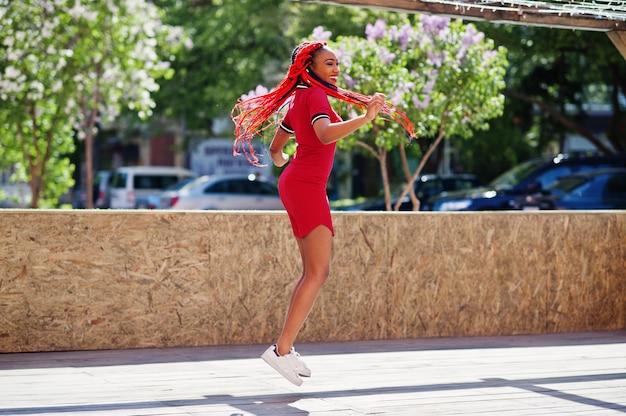Ładna i szczupła kobieta w czerwonej sukience z dredami w ruchu, zabawy na ulicy