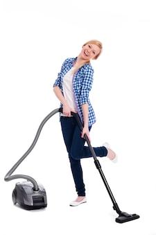 Ładna i uśmiechnięta kobieta odkurza podłogę