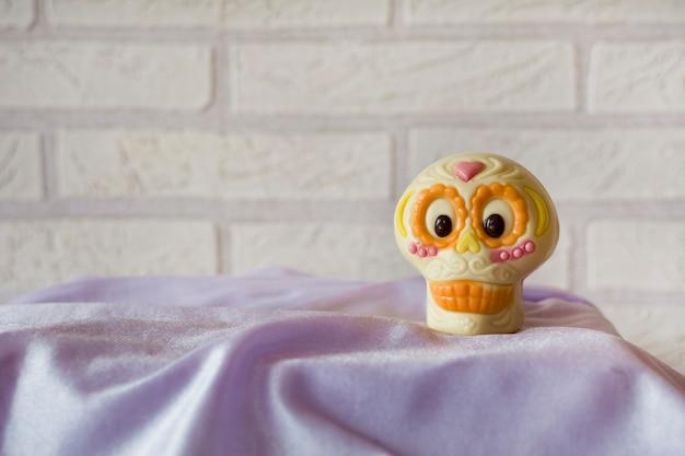 Ładna i zabawna biało-pomarańczowa czaszka catrina na fioletowym materiale.