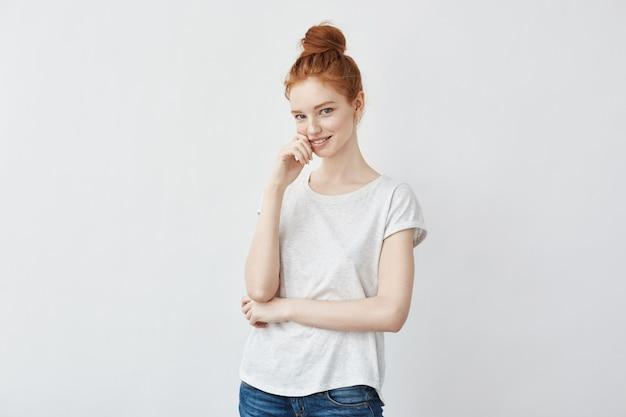 Ładna imbirowa kobieta z modną koką, uśmiechając się, patrząc prosto.