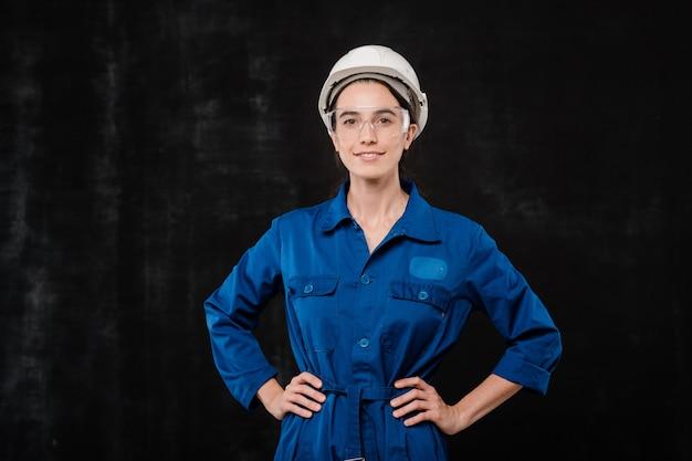 Ładna inżynierka w niebieskiej odzieży roboczej, okularach ochronnych i hełmie, trzymając ręce w pasie na czarnym tle