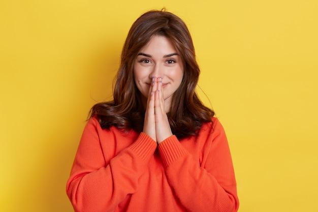 Ładna kaukaska kobieta trzyma dłonie razem, ma zadowolony wyraz twarzy, prosi o coś, wygląda na zadowoloną, ubrana w pomarańczowy luźny sweter, stojąca na żółtym.